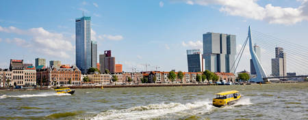 Water taxi on the Maas river in front of Rotterdam skyline